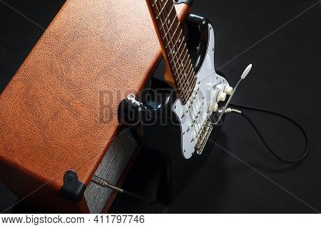 Tube Combo Amplifier For Electric Guitar With Black Guitar On The Black Background.