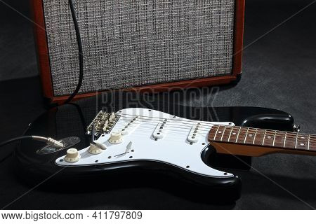Brown Amplifier For Electric Guitar With Black Guitar On The Black Background.