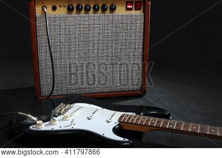 Brown Combo Amplifier For Guitar With Black Guitar On The Black Background.