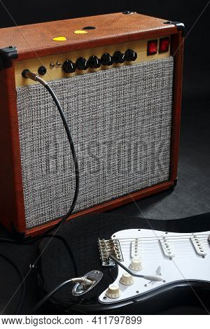Brown Guitar Amplifier With Black Guitar On The Black Background.