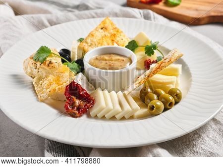 Cheese Food Plate with Olives and Greens. French appetizer cheese board. White restaurant plate on grey table. Wine snacks, gourmet, delicatessen, rustic food concept