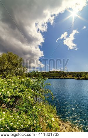 Summer Landscape With Flowers, Green Plants, Lake With Water, Dark Clouds On The Horizon And Sun Ris