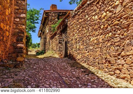 Narrow Cobbled Street With Rustic Stone Houses And Old And Medieval Atmosphere.