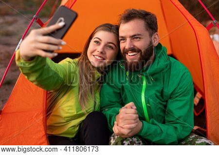 Cheerful Male And Female Travelers In Outerwear Smiling And Taking Selfie Near Tent While Resting On