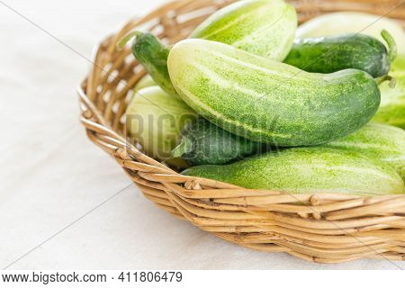 Close Up Group Of Fresh Organic Cucumber Or Zucchini In Wood Basket On White Table. Cucumber Or Zucc