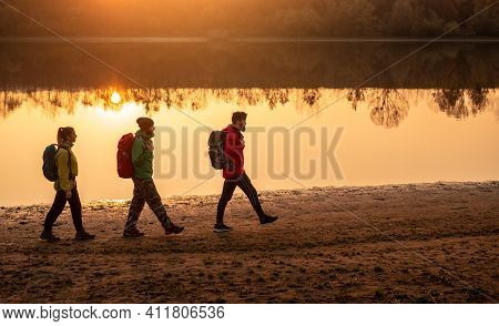 Side View Of Men And Woman With Backpacks Hiking On Shore Near Calm River During Trip In Countryside