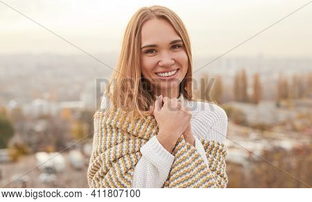 Happy Young Woman In Knitted Sweater Wrapping In Warm Scarf And Smiling For Camera On Blurred Backgr