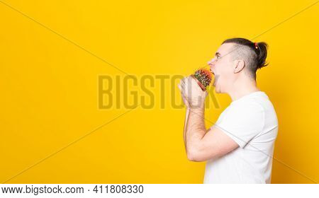Funny Young Man Bites A Cactus In A Pot. Man Tries To Bite Off A Cactus On A Yellow Background. Bann