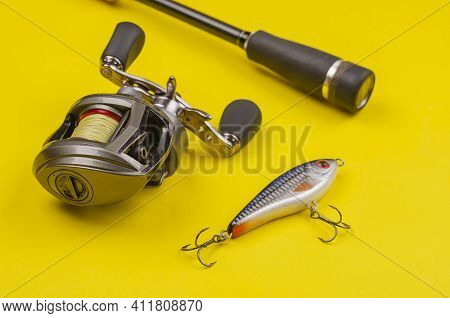 Fishing Tackle For Predatory Fish. Fishing Rod With Reel And Bait On Yellow Background. Casting Rod