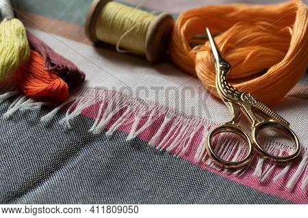 Different Embroidery Equipment On The Table - Fabric, Skeins With Floss Threads And Scissors