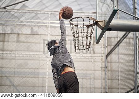 Young Asian Adult Man Basketball Player Attempting A Dunk On Outdoor Court