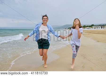 Happy Mom And Daughter Walking On The Sea Beach Holding Hands. Family Middle-aged Mother And Preteen