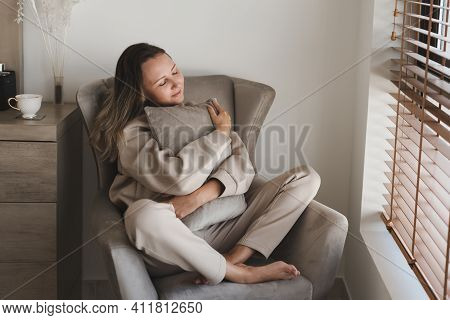 Caucasian Woman Dressed In Comfy Grey Loungewear Sitting In A Cozy Armchair In Her Bedroom And Holdi
