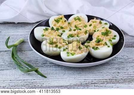 Stuffed Eggs With Crab Sticks, Mayonnaise, Cheese And Green Onion On Black Plate. White Background