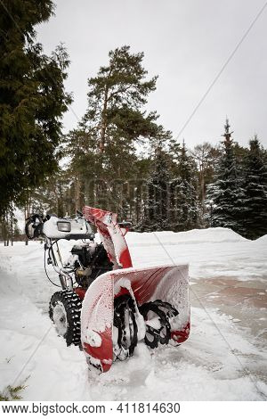 A Red Snow-covered Snow Blower Stands On The Road After Clearing The Area. Clearing The Area From Sn