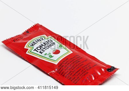 Umea, Norrland Sweden - January 21, 2021: A Disposable Package Of Tomato Ketchup On A White Backgrou