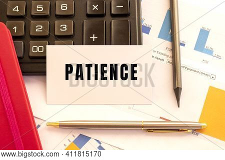 Text Patience On White Card With Metal Pen, Calculator And Financial Charts. Business And Financial