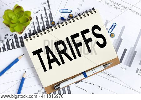 Tariffs. Text On White Notepad Paper On Light Background