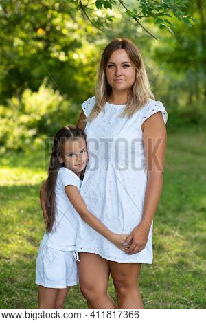 Little girl hugs her mother in summer forest nature outdoor. Portrait of mom and daughter. Family walks barefooted in park. Trust, kindness, maternity, parenthood, confidence, mother's love concept.