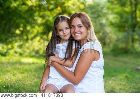 Little girl hugs her mother in summer forest nature outdoor. Family, trust, kindness, maternity, parenthood, confidence, mother's love concept.