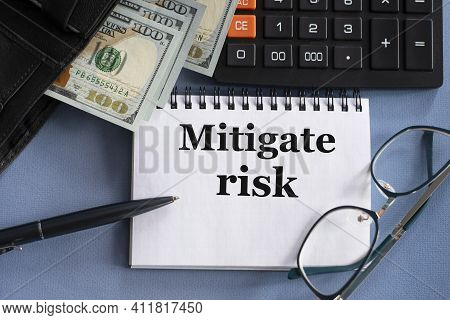 Mitigate Risk - Words In A Notebook Against The Background Of Money, Glasses And Calculator. Educati