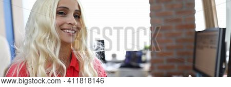 Woman In Wig With White Hair Sits At Table And Smiles. Changing Appearance With Wigs Concept