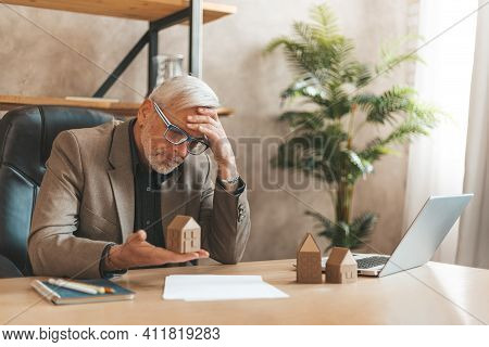 Overdue Mortgage Payment. Senior Man Holding A Model House In His Hands In Despair. Pledged Housing,