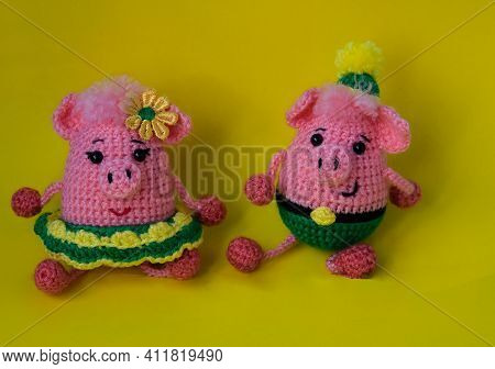 A Couple In Love, A Family Of Two Knitted Toy Piglets. Pink Piglets Boy And Girl, Crocheted On A Yel