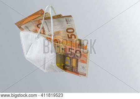 Medical Ffp2 Face Mask Against Covid-19 Virus Filled With Euro Banknotes, Concept For Enrichment By