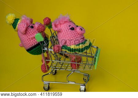 Two Pink, Crocheted Little Pigs A Girl And A Boy On A Yellow Background. A Pig Is Sitting In A Shopp