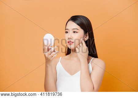 Beauty Portrait Of A Happy Attractive Woman Examining Her Face While Looking At The Mirror Isolated