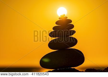 Balanced Pebble Pyramid Silhouette On The Beach. Abstract Warm Sunset Bokeh With Sea On The Backgrou