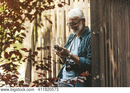 A Mature Man With A Beard Is Using The Dating Service And Smiling. Online Search For A Love Partner.