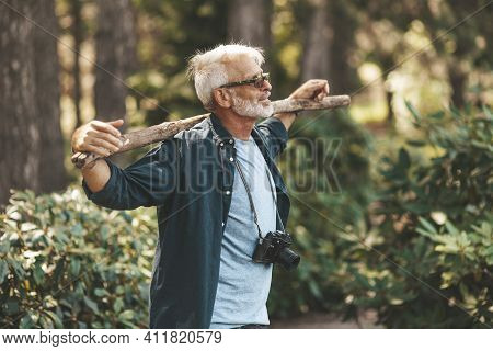 A Mature Bearded Grandfather Holds A Stick On His Shoulders. A Pensioner Man Enjoys Life, Walking In