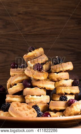 Many Small Round Waffles Lie On A Plate On Top Of Each Other And Are Poured On Top Of Honey. Waffles