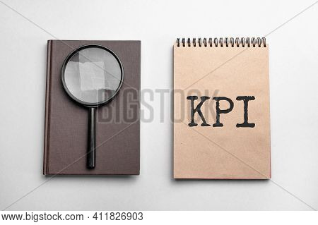 Craft Colour Notepad With Text Kpi. Notepad With , Magnifying Glass. Business Concept