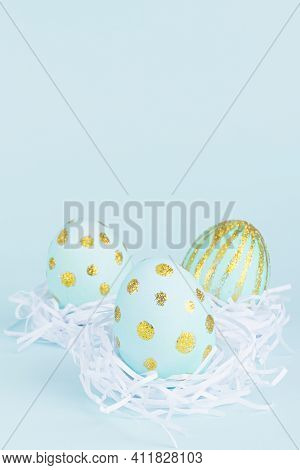 Simplicity And Minimal Design Of Easter Eggs With Gold In White Nest On Blue Background, Vertical.