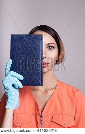 Attractive Young Female Doctor In Orange Medical Jacket With Notebook