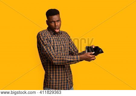 Shocked Black Guy Showing Empty Wallet At Camera, Suffering From Poverty And Absence Of Money, Emoti