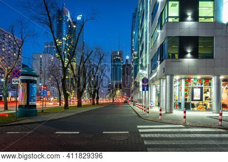 Warszawa, Poland - February 25, 2021: Amazing cityscape of Warsaw with metro station entrance by night, capital of Poland.
