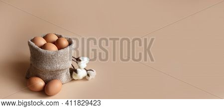 Beige Chicken Eggs In A Canvas Burlap Bag With Cotton Flowers.