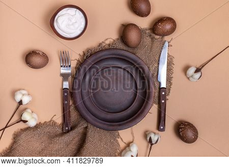 Ceramic Plate On Burlap Cloth With Easter Eggs, Cream Bowl And Cotton Flowers