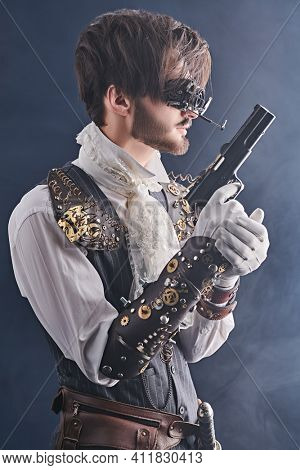 Portrait of a handsome noble man with steampunk gadgets and a gun on a dark background with haze. Steampunk man.