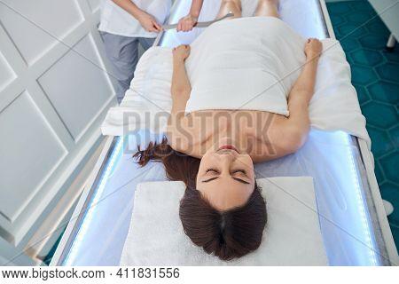 Massagist Scraping Female Leg With Long Gua Sha Instrument
