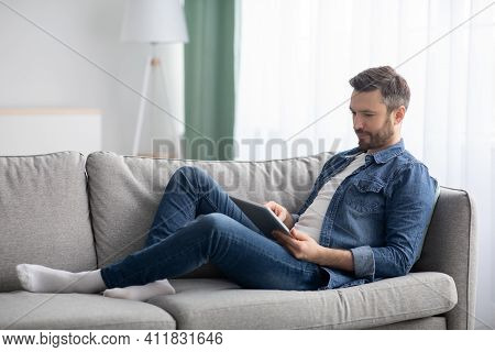Happy Middle-aged Man In Casual Laying On Couch At Home, Using Digital Tablet, Copy Space. Handsome