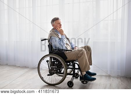 Full Length Portrait Of Handicapped Senior Man In Wheelchair Feeling Desperate And Lonely, Looking O