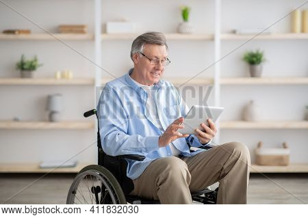 Joyful Impaired Senior Man In Wheelchair Using Tablet Computer At Home. Positive Retired Male With P