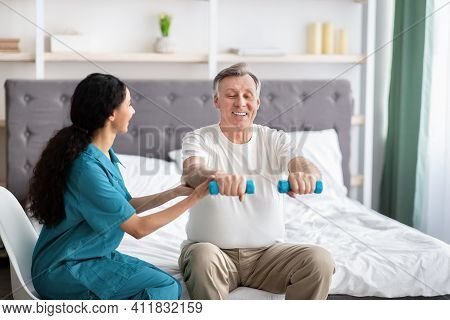 Young Physiotherapist Helping Homebound Elderly Man To Do Physical Exercises With Dumbbells On Bed A