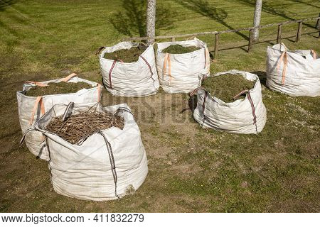 Group Of Sacks Full Of Cut Grass. Gardening In Public Spaces