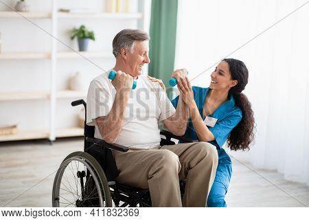 Millennial Physiotherapist Helping Disabled Elderly Man In Wheelchair To Work Out With Dumbbells, To